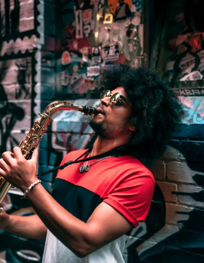 Afro hairstyle young male playing saxophone