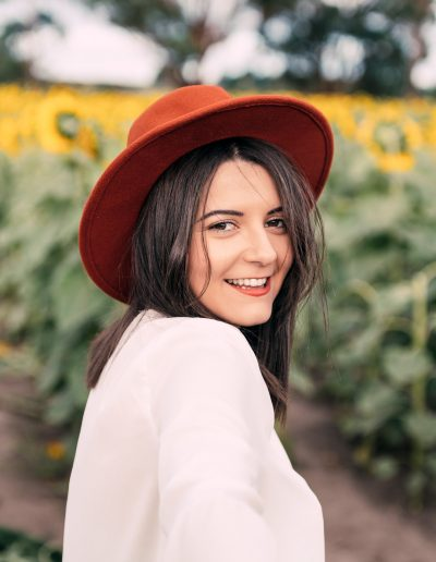 Brunette girl with hat in a sunflower field