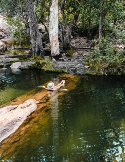 A woman swimming in a natural pool