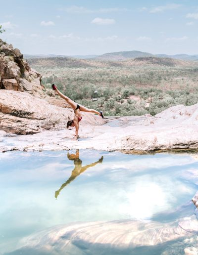 A young woman does the split in a natural pool of Australia