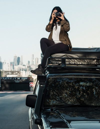 Asian backpacker girl with camera on top of car