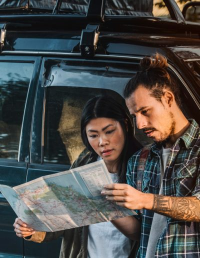 Backpackers checking map before driving